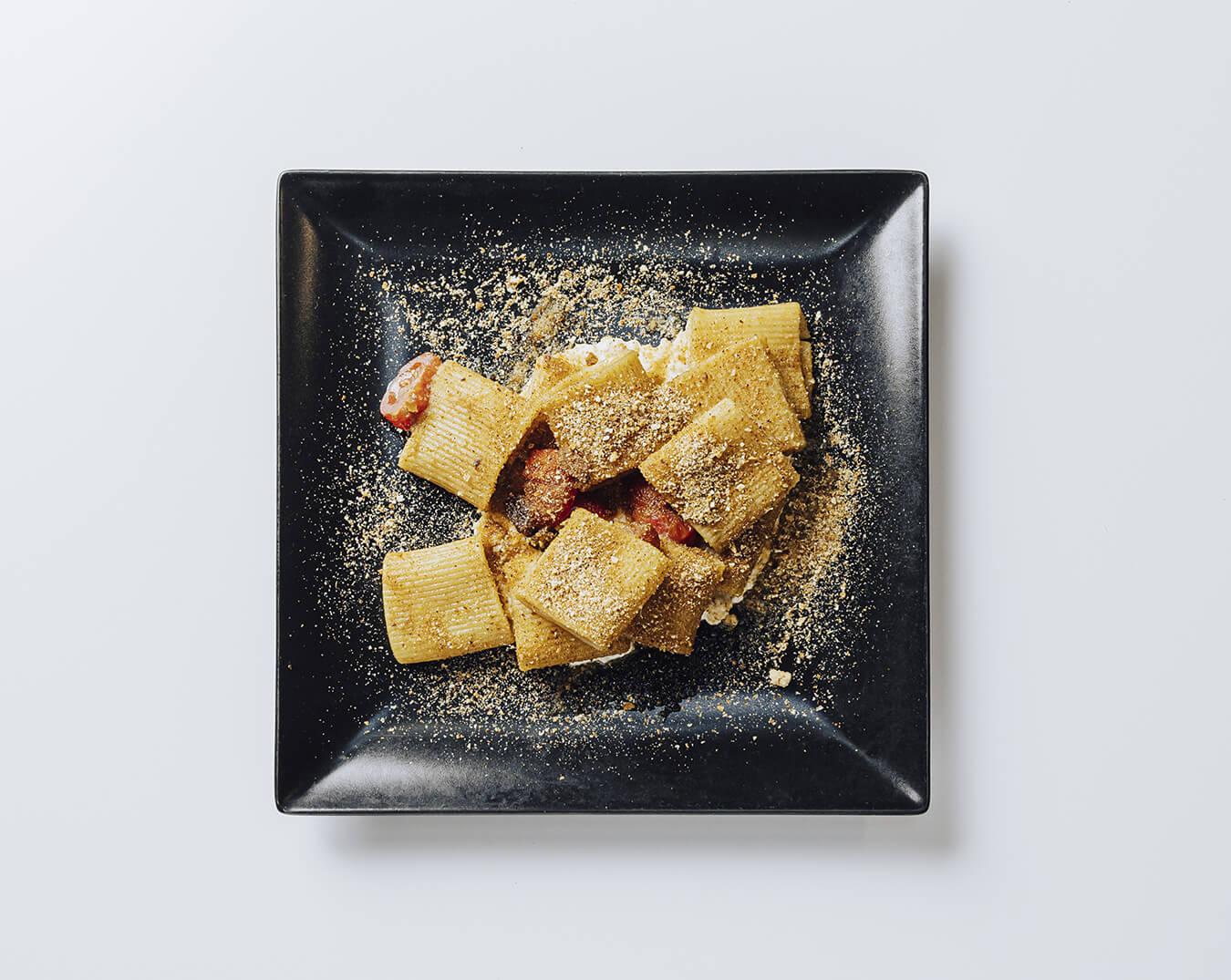 Mezzi paccheri con alici, pomodorino, uvetta, crema di ricotta e pan tostato